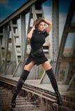 Attraktiv kvinna med den korta svarta klänningen och långa läderkängor som står på stängerna med bron i bakgrund sexig modeflicka Royaltyfria Bilder