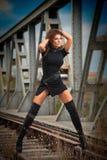 Attraktiv kvinna med den korta svarta klänningen och långa läderkängor som står på stängerna med bron i bakgrund sexig modeflicka Arkivbild