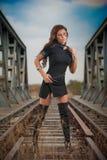Attraktiv kvinna med den korta svarta klänningen och långa läderkängor som står på stängerna med bron i bakgrund sexig modeflicka Arkivfoton
