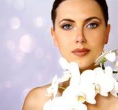 Attraktiv kvinna med den vita orkidén Fotografering för Bildbyråer