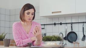 Attraktiv kvinna med hörlurar som talar i hennes kök arkivfilmer