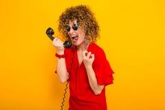 Attraktiv kvinna med kort lockigt hår med telefonen royaltyfria bilder