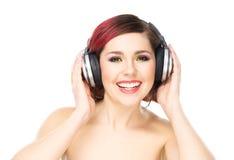 Attraktiv kvinna med kulört hår som tycker om musiken Fotografering för Bildbyråer