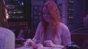 Attraktiv kvinna med lockigt derhår som äter maträtten i modern stång eller restaurang och visar det reko tecknet som ser i stock video