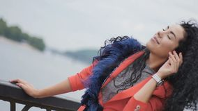 Attraktiv kvinna med lockigt hår på bron stock video