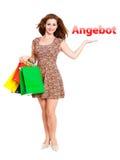 Attraktiv kvinna med shoppingpåsar och erbjudande gest Royaltyfri Foto