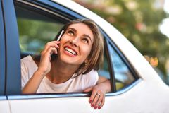 Attraktiv kvinna med telefonen i bilen, solig dag Fotografering för Bildbyråer