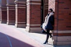 Attraktiv kvinna mot väggkolonnen Arkivfoton