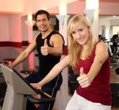 Attraktiv kvinna och en man som cyklar i en idrottshall Arkivfoton