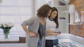 Attraktiv kvinna- och kvinnligsäljarekonsulent som ser på smycken till och med ställa ut Royaltyfri Foto