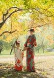 Attraktiv kvinna och liten flicka i en kimono som går i parkera royaltyfria bilder