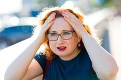 Attraktiv kvinna på knipet för huvud för gatakänsla den plötsliga - migränattack arkivfoton