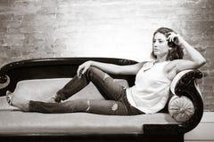 Attraktiv kvinna på soffan Arkivfoto