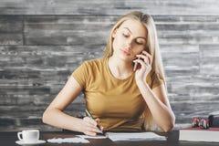 Attraktiv kvinna på telefonen som gör skrivbordsarbete Royaltyfri Foto