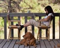 Attraktiv kvinna på trädäck med hunden och bärbara datorn Arkivbild