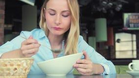 Attraktiv kvinna som äter smaklig soppa i kafé i staden stock video