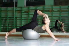 Attraktiv kvinna som övar med övningsbollen royaltyfria foton
