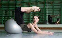 Attraktiv kvinna som övar med övningsbollen royaltyfria bilder
