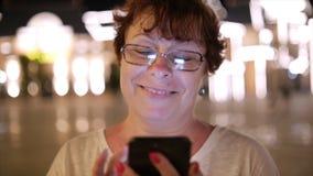Attraktiv kvinna som använder en mobiltelefon, medan gå till och med gatorna i en nattstad, i bakgrundsnattstaden lager videofilmer