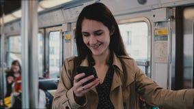 Attraktiv kvinna som använder smartphonen i tunnelbanabil Härlig ung europeisk flicka i den sociala nätverksrengöringsduken app d arkivfilmer