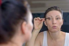 Attraktiv kvinna som applicerar mascara till henne snärtar royaltyfri foto