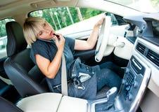 Attraktiv kvinna som applicerar smink i hennes bil och talar på mobi Arkivfoto
