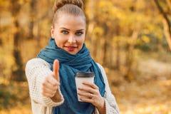 Attraktiv kvinna som dricker coffe och visar thumbup Arkivbilder