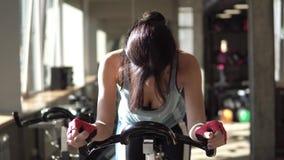 Attraktiv kvinna som förhöjer hennes uttålighet, medan utarbeta på en exercycle arkivfilmer