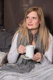Attraktiv kvinna som framåtriktat ser till hennes varma drink från koppen Royaltyfri Bild