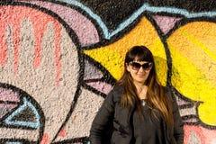 Attraktiv kvinna som framme poserar av grafitti Arkivfoto
