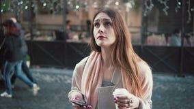 Attraktiv kvinna som framme står av show-fönster och dricker te Brunettflickan drömmer för att köpa något, suckar Arkivfoto