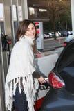 Attraktiv kvinna som fyller henne bil med petrol royaltyfri bild