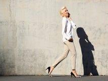 Attraktiv kvinna som går och talar på mobiltelefonen Royaltyfri Foto