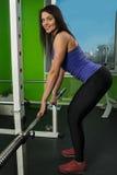 Attraktiv kvinna som gör övning med viktstången Arkivbild