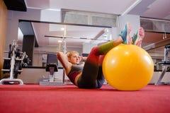 Attraktiv kvinna som gör Push-UPS med bollen arkivbild