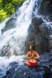 Attraktiv kvinna som gör yogaövningen som poserar med händer på henne tillbaka under den härliga tropiska vattenfallet som in får Arkivbild