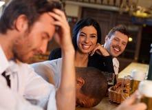 Attraktiv kvinna som har gyckel med vänner i bar Royaltyfri Fotografi