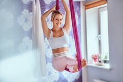 Attraktiv kvinna som hemma kopplar av på en purpurfärgad hängmatta, flyg- anti--gravitation för övningar yoga royaltyfri fotografi