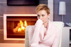 Attraktiv kvinna som hemma sitter vid spis fotografering för bildbyråer
