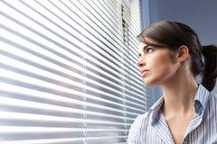 Attraktiv kvinna som kikar till och med rullgardiner Arkivbild