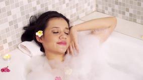Attraktiv kvinna som kopplar av i badkar stock video