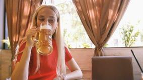 Attraktiv kvinna som kopplar av i kafét och dricker öl arkivfilmer