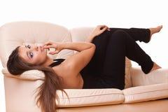 Attraktiv kvinna som lägger på sofaen Fotografering för Bildbyråer