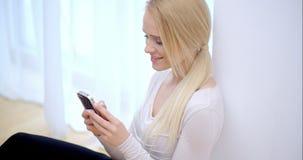 Attraktiv kvinna som läser ett meddelande på hennes telefon arkivfilmer