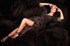 Attraktiv kvinna som ligger med hennes händer vid hennes huvud och poserar för kamera Arkivfoto