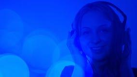Attraktiv kvinna som lyssnar till färgrik bakgrund för musik Royaltyfri Foto