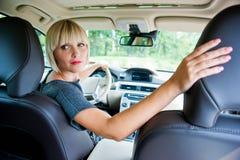 Attraktiv kvinna som parkerar hennes bil fotografering för bildbyråer