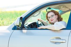 Attraktiv kvinna som poserar i bil på chaufförplats arkivfoto
