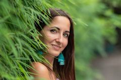 Attraktiv kvinna som poserar med ett leende nära det gröna staketet, närbild royaltyfria bilder