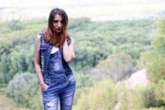 Attraktiv kvinna som poserar mot bakgrunden av skogen Arkivbild